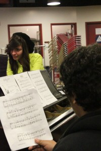 Looking over choral music during Jazz Choir Seniors Jonny Arenas and Angelica Villarreal practice their parts by the piano. Both Arenas and Villarreal auditioned and were accepted into the All-State Jazz Choir, one of the highest high school groups in music.