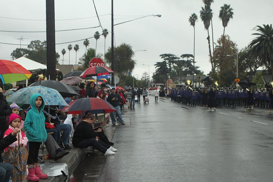 Young parade observers look on, waiting in the rain, for the final Downey Parade participants along Downey Avenue, on Dec. 3, at three in the afternoon. Despite the weather crowds of spectators turned out to watch the numerous marching bands, Latin dancers, drill teams, and other participants stride through the city.