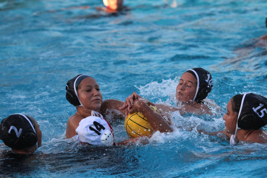 A lose ball of a counter attack sends Olivia Aguirre, 11, Alex Perez, 10, and Meghan Nevarez, 12, to try to regain possession of the ball as they take on the Whittier High School Cardinals in the Downey Aquatics Center on Dec. 11. The lady vikes kept their winning strike, as the final score was 11-9.