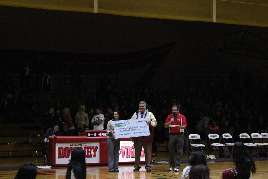 On January 9, WalMart representative Sara Arroyo presents a $1,000 dollar check to Mr. Houts, at half time in the DHS gymnasium.