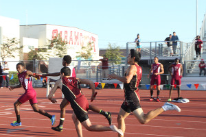 One of three hand offs is made by Ismael Guerrero,12, to Anthony Bravo,11, for the second leg of the boys 4x4 relay race on Mar. 27, at Paramount High School.