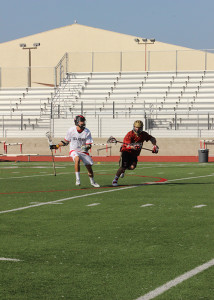"""At the varsity lacrosse game vs. Palos Verdes on March 4, captain Nick Farina, 12, defends the ball from the opponent, making a goal. """"Over forty different colleges have scouted me this year,"""" Farina said. """"I have decided to go to Adam State in Alamosa, Colorado."""""""