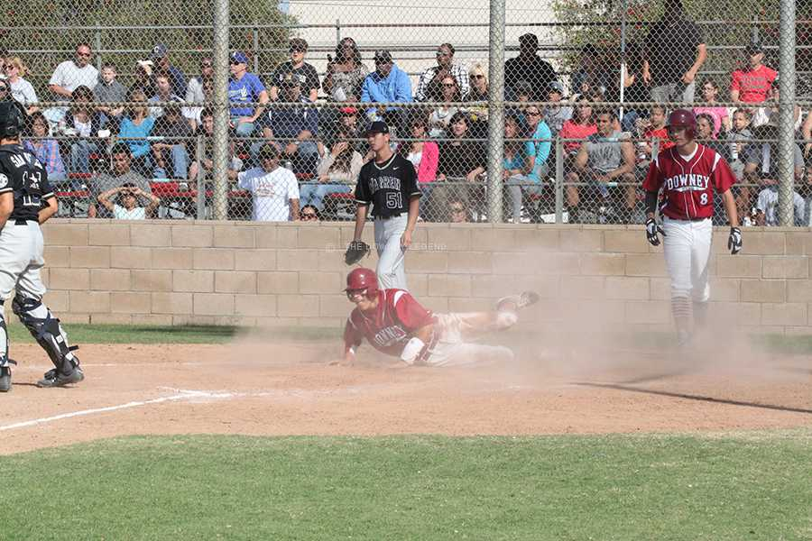 At the Downey baseball field, Ernest Davila slides into and over the home plate against crosstown rival Warren on Friday, April 12, to gain a point against the Bears. Davila's slip into safety and home plate was not enough to secure a victory for the Vikings.