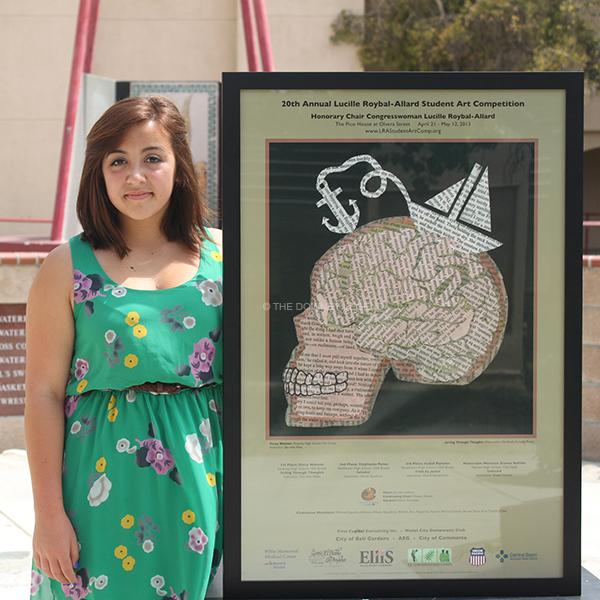 "On May 24, Daisy Watson displays a copy of her old book art as the first place winner of the 20th Annual Lucille Roybal- Allard Student Art Competition. ""I named my art Sailing Through Thoughts because sometimes you recap into the past, "" Watson said. "" It is better to pass them in order to move into future goals."""