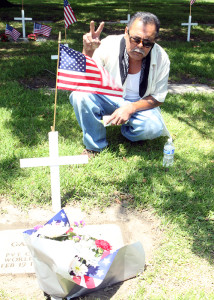 After the Memorial Day tribute concluded at the Downey Cemetery on May 27, Anthony Munoz puts up a peace sign as he kneels by the grave of his uncle, Gabino Munoz, to remember and acknowledge his legacy. Gabino Munoz was wounded in action in Germany during WWII, and received a Purple Heart.