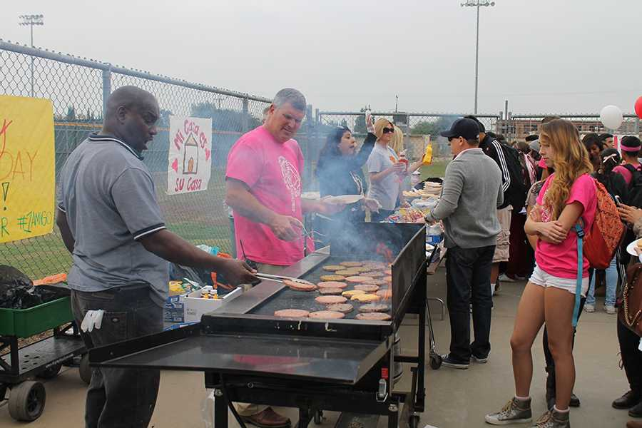 """On Thursday, Oct. 24, Mr. Houts and Mr. Bracey cook hamburgers at the third annual Amigos barbeque behind the Allen Layne Stadium. """"Let's get these burgers going, the Amigos are starving,"""" Houts said."""