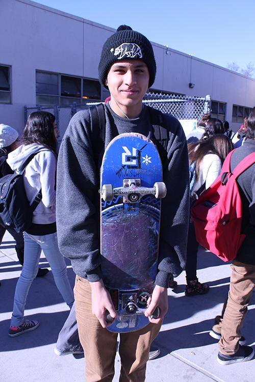 """On Wed., Dec. 11, David Mercado, 9, gets his skateboard signed by Mike Smith in the gym.  """"I just had to get my board signed by Mike,"""" Mercado said. """"It's amazing how he created the Skate for Change organization."""""""