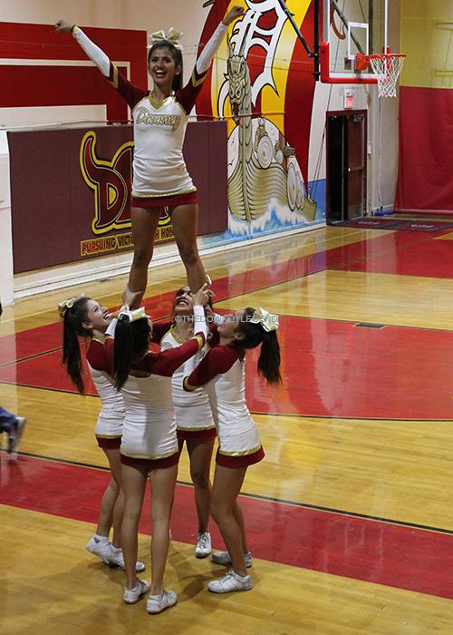 In the gym, the varsity cheerleaders throw up a high v during halftime on Tues., Jan. 14. The flyers practiced often, in order to perfect the stunt.