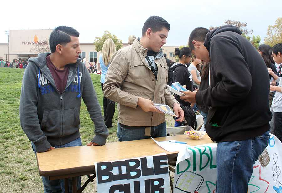On Wed., Feb. 26, president of Bible Club, Francisco Porra, 12, hands out flyers to students who pass by the club table during club rush. Bible Club handed out Jolly Ranchers to those who signed up for the club.