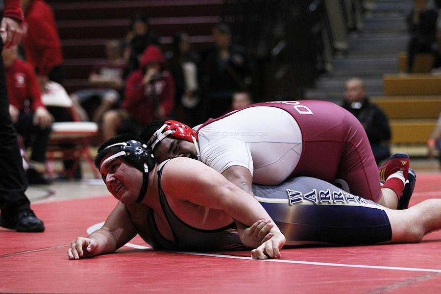 """On Jan. 15, in the gym during a wrestling match against Warren, Angel Baez, 12, goes for a pin against a Warren wrestler. """"Before each match I try to get into my zone, so I can just focus on the match,"""" Angel Baez said."""