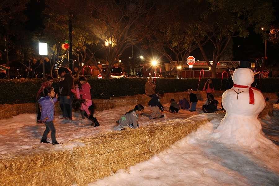 Parents and children enjoy themselves at the tree lighting ceremony by running and playing in the parking lot where the fake snow was set up for them. Some children saw snow for the very first time.