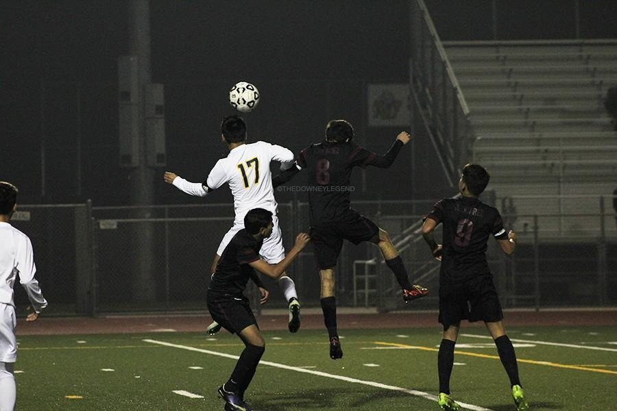 """Downey plays against Warren, at Justice Stadium on Feb. 3, where captain Joshua Hernandez (#8) goes for a header to pass the ball to another teammate. """"It was late in the game, and I was trying to give the team an extra push for momentum,"""" Hernandez stated."""