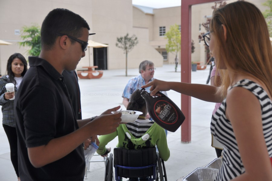 Getting chocolate sauce poured on his ice cream, Eduardo Ubillus, 11, chats with another student on June 4, outside the J building. Ubillus enjoyed working with the students in Cramm's class.