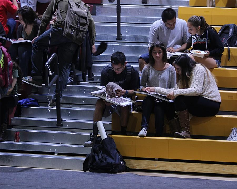 """On June 3, senior Nicole Parra, looks through the yearbook with her friends, during the yearbook distribution party in the gym. """"I liked looking at every page and remembering everything that happened my senior year,"""" Parra said. """"I'm happy I bought it because it is my last year at Downey High."""""""
