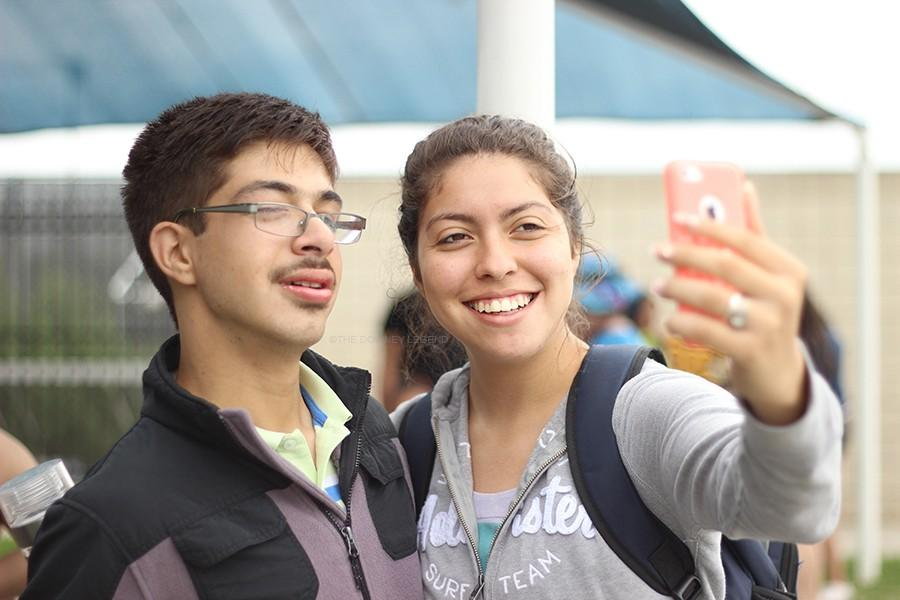 """At the Amigos Club Pool Party on June 3, at Downey High's pool, seniors Valerie Ortiz and Cesar Cesrbans take a picture to remember the moment. """"I love taking selfies on Snapchat with my amigos friends,"""" Valerie Ortiz said, """"because I want to share with the people the darnedest thing they say that make me crack up and I never want to forget them, and I never will."""""""