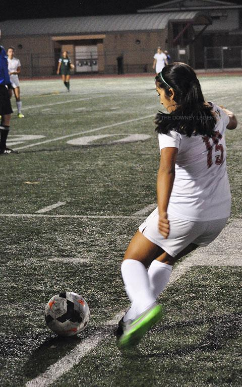 """Fighting for a victory against Long Beach Poly, senior Brittany Reynoso crosses the ball on the 25 yard line. """"We like to say no maybes because it basically means don't doubt yourself,"""" Reynoso said, """"and commit to whatever you want to do."""""""