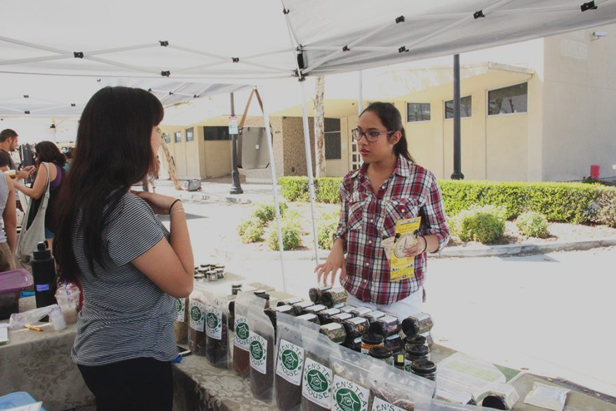 At the Downey farmers' market on 3rd Street, on October 1, Kimberly Garcia asks Zeus Tea House vendor Crystal what tea she personally would choose. She works for the company where some tea blends are made especially for the business, and her personal favorite tea is the peach oolong.