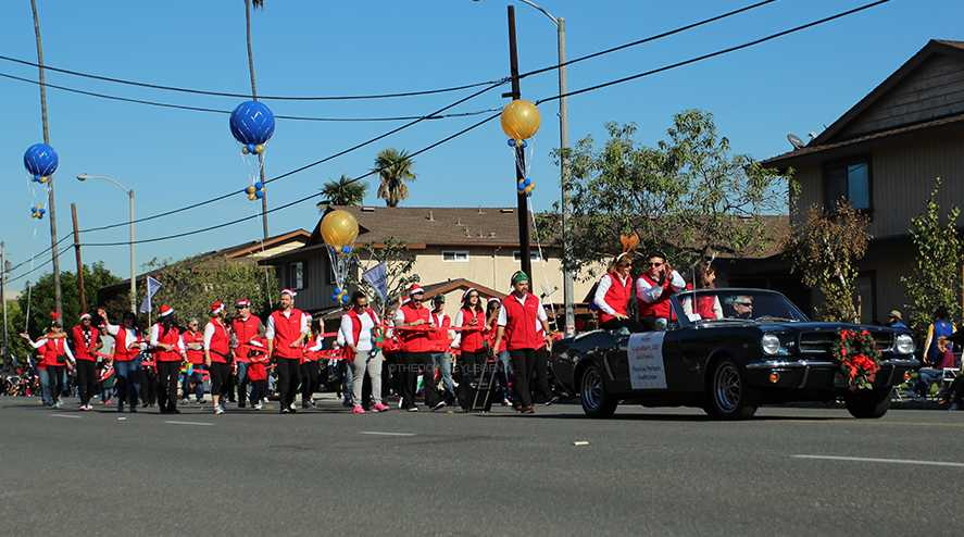 Opening up the parade in a black convertible, Financial Partners, with their members walking behind them, participate on Dec. 4th for Downey's Christmas Annual Parade. Every year, people from the city line up to see the show that runs through Florence and 3rd St.