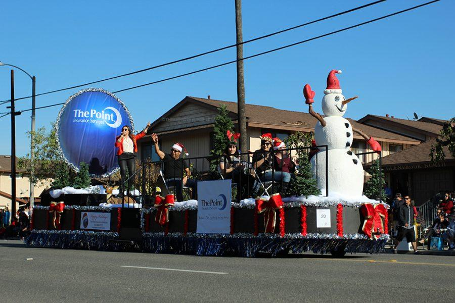 During the Downey Annual Christmas Parade on Dec. 4,  entertainers perform their routine as they go down the street, including a float named, The Point, which is an insurance company. Performers who sang and danced, participated in the parade while being carried on floats down Florence to the end of 3rd St.