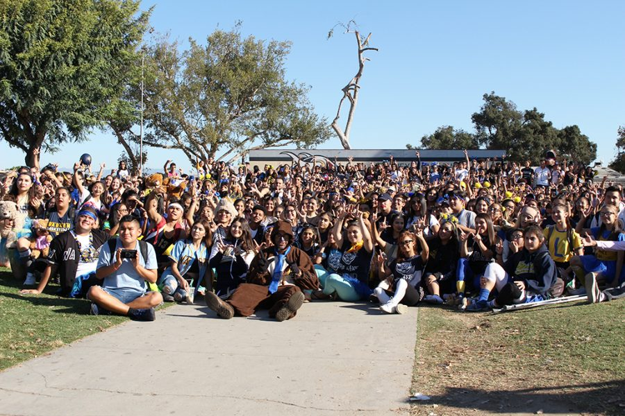 """Warren Wimps come to together in front of the main stage, to celebrate the annual tradition of the city's high school rivalry on Oct. 26. Students stood together smiling and chanting: """"What do we eat? Bear Meat,"""" before snapping the photo."""