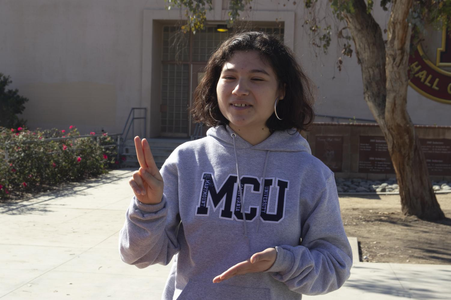 In+front+of+the+J+building+on+Feb.+8%2C+Priscilla+Palos%2C12%2C+communicates+using+sign+language+to+her+interpreter+and+mentions+her+acceptance+to+Gallaudet+University+in+Washington+D.C.+%E2%80%9CMy+ASL+teacher+told+me+about+it+and+at+first+I+didn%E2%80%99t+want+to+go%2C%E2%80%9D+Palos+said.+%E2%80%9CI+didn%E2%80%99t+think+Gallaudet+would+be+for+me+but+I+learned+more+about+it+and+signed+up.%E2%80%9D+