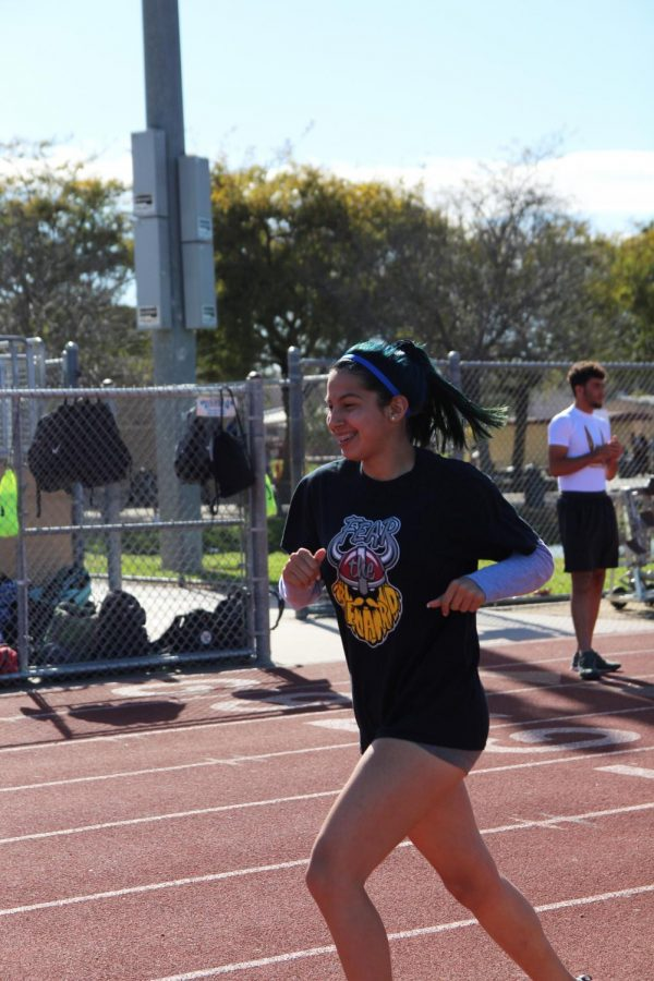 """Warming up on the track, Vanity Arroyo, 12, practices for her track meet coming up on Mar.13 and talks about how she balances school work and track. """"I try to get as much done during school and right after practice,"""" Arroyo said. """"When I get home I start on my homework before anything else."""""""