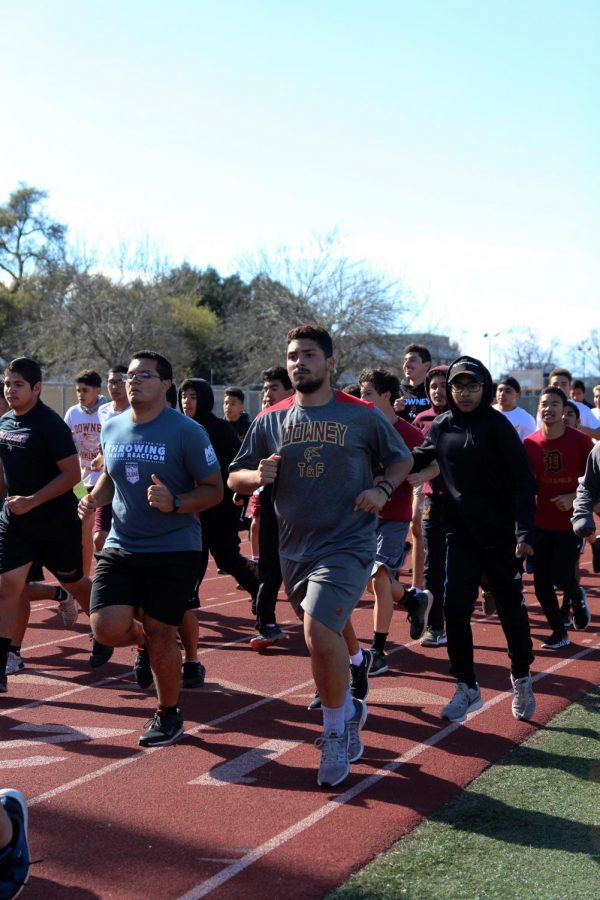 """Downey boys track and field running their warm up laps before practice on Mar. 8, front and center, Daniel Bravo, 12, stays motivated and puts in all his effort when doing shot put. """"I work hard in lifting and throwing,"""" Bravo said. """"I want to be on the wall of people that went to CIF so that a small part of me can be forever recognized just like my brother."""""""