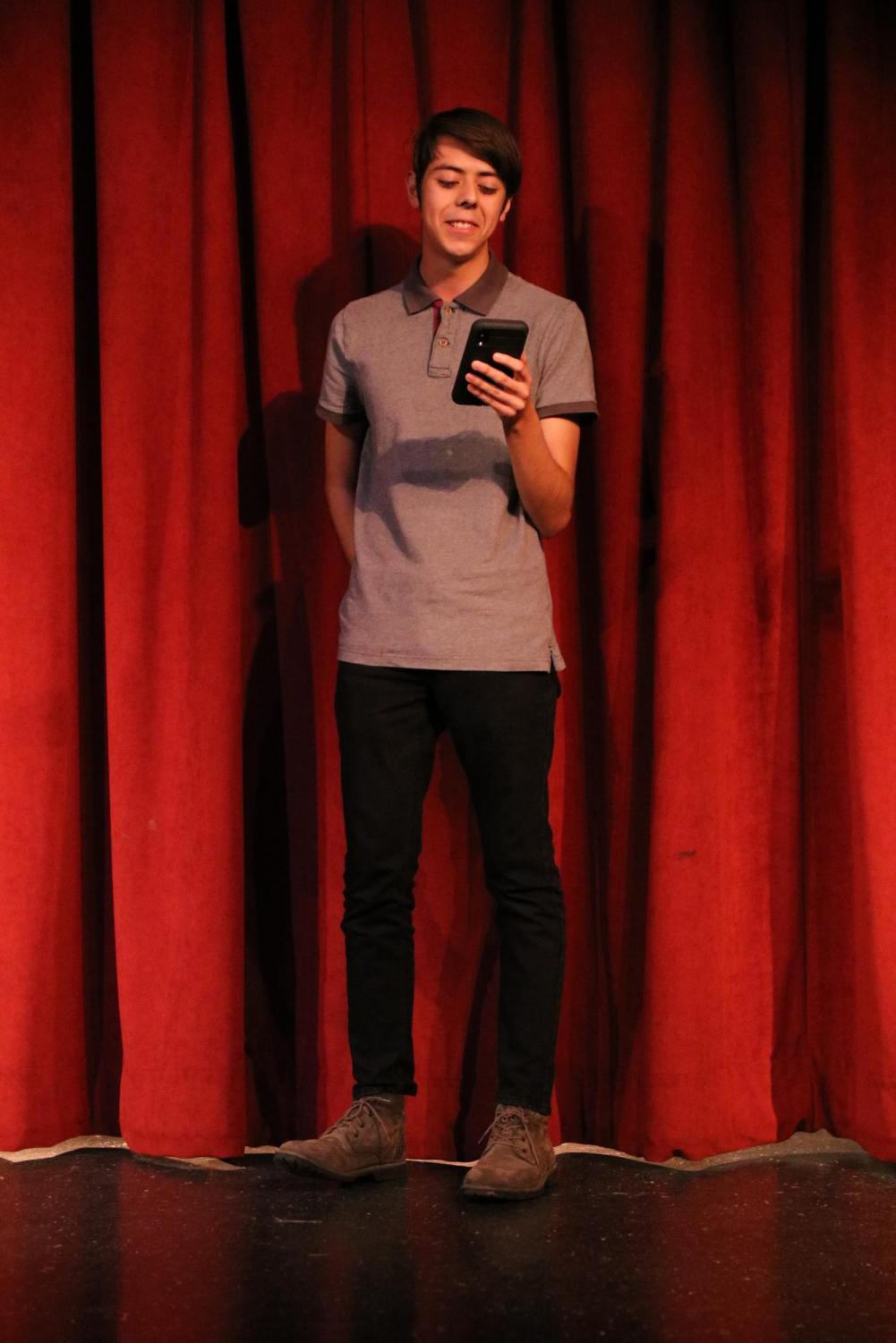 Reciting+two+poems%2C+Edward+Haro%2C+12%2C+performed+at+the+Writing+Center%E2%80%99s+Poetry+Slam+on+Feb.+28+in+the+Downey+High+Theater.+%E2%80%9CI+tried+making+any+dialogue+within+it+%28the+poem%29+different%2C+I+did+this+by+changing+the+accents+and+stuttering+similar+to+how+the+boy+in+the+poem+did%2C%E2%80%9D+Haro+said.+%E2%80%9CI+chose+these+poem+because+I+just+wanted+people+to+know+how+great+they+were.%E2%80%9D