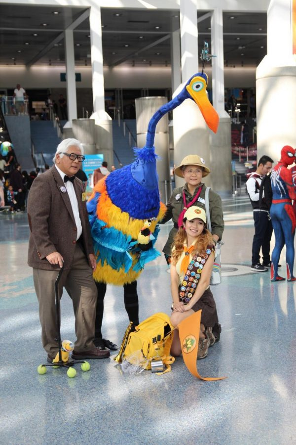 All having similar interests, these Comic-Con attendees posed for photos, cosplaying as main characters from Disney film, Up. Originally attending separately, Mr. Fredrickson (the elderly man) and Russell (the young lady on her knees) join Mrs. Fredrickson (the elderly lady) and Kevin (bird), in posing for photos.