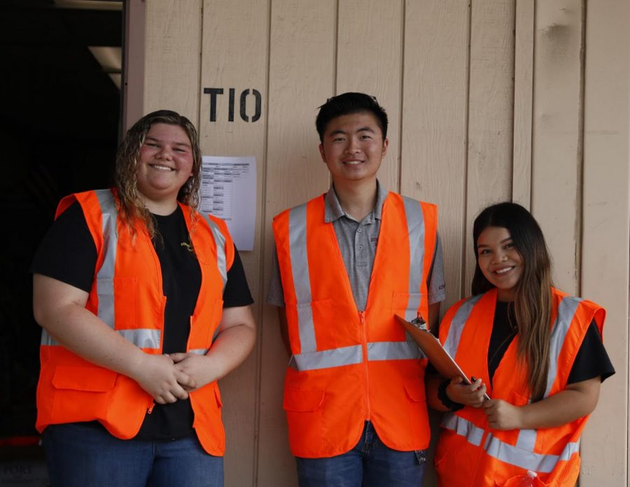 """Guiding DHS students in bright orange vests during the earthquake drill, Senior Sports Medicine students, Alyssa Fetter, Jason Gov, and Carla Chafloque, aid in assessing the drills and emphasize the importance of preparing for similar situations. """"Students need to be taking these drills seriously because they're scary,"""" Chafloque said. """"If there were to be an actual earthquake, people would most likely panic which is why we need to be prepared."""""""