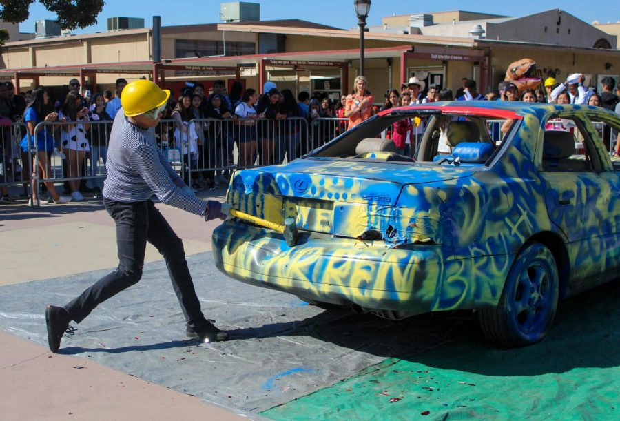 Vikings did not fail in making dents on the Warren decorated car with a sledgehammer. Many students stood, observing the Viking at work.