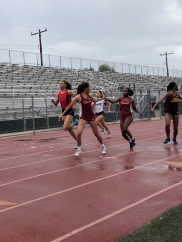 "While doing a handoff in the girls varsity 4x200, senior Mikala Fletcher was second leg in the event receiving the baton from junior, Bryanna Anderson. ""The 4x200 is a really fun event because it only happens on relay meets so it's fun to do it when I get the chance,"" Fletcher said. ""This is my last high school track season and I'm pretty eager to finish strong."""