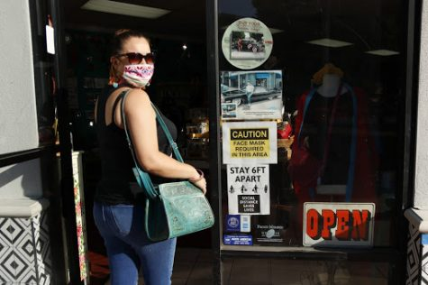 "As small businesses have been greatly impacted by the pandemic,  Uptown Whittier small business owner, Yolanda Garcia (photographed above), opens up Casita Del Pueblo; mask on, ready to start business up again with new guidelines. ""I've had to rearrange the store so customers can be 6ft apart as well as put up posters with safety precautions,"" Garcia said. ""Store hours have had to be slightly changed due to less traffic coming in and sales not being where they were before."""